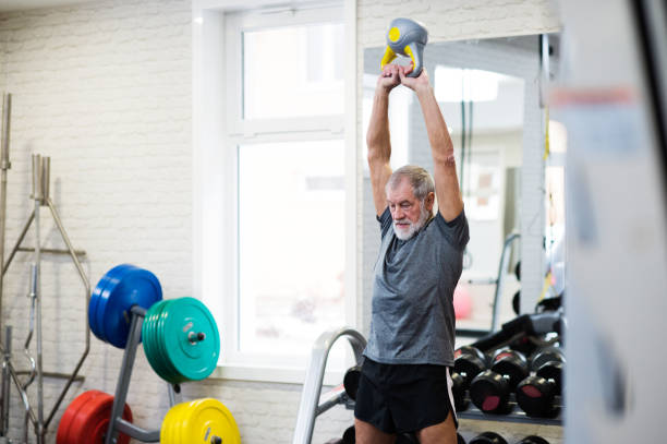 Senior man in gym working out using kettlebells. - foto stock