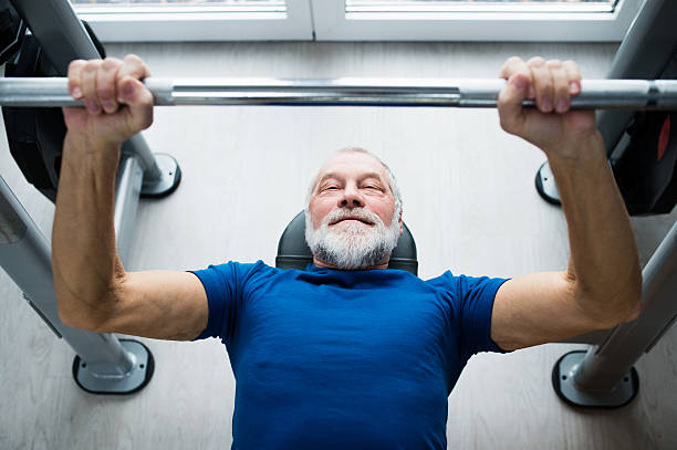 Senior man in gym working out with weights, bench pressing. stock photo