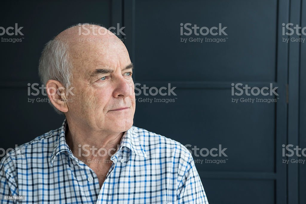 Senior man in his 70s looking away against grey background stock photo