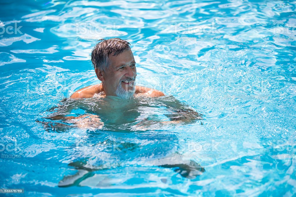 Senior man in his home swimming pool stock photo