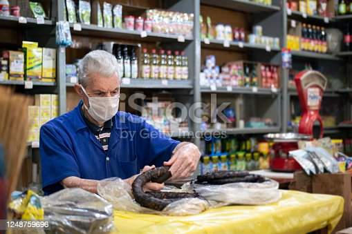 Photo of a senior man in his small grocery store.