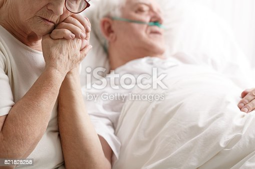 909569706istockphoto Senior man in hospital bed and his wife holding his hand 821828258