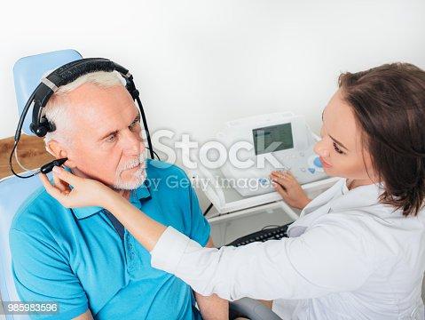 istock Senior man in hospital having ear test. 985983596