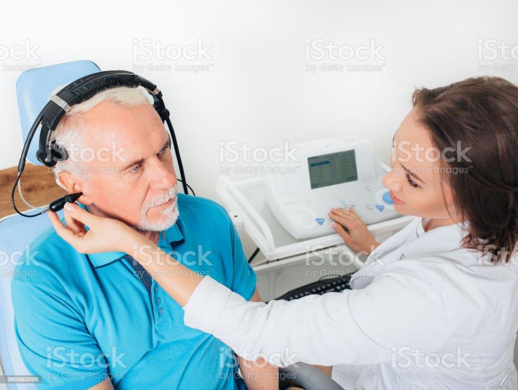 Senior man in hospital having ear test. stock photo