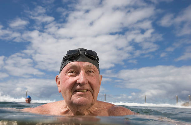 Senior man in infinity pool, close-up stock photo