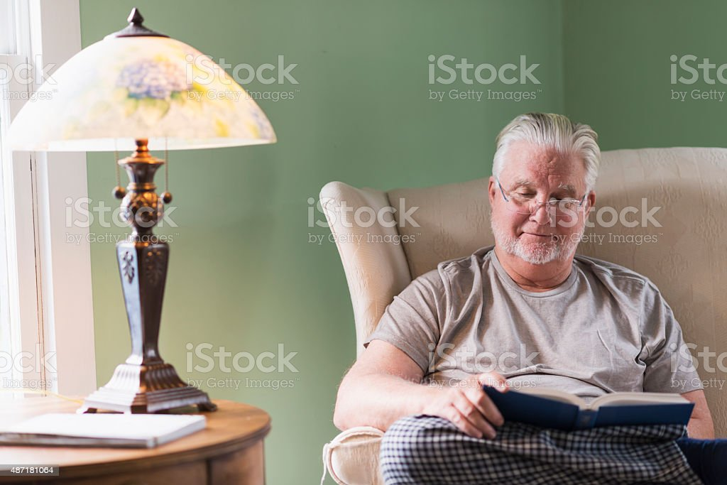 Senior man in living room reading book stock photo