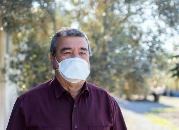 hogere mens in medisch masker- coronavirus - verduisterd gezicht stockfoto's en -beelden