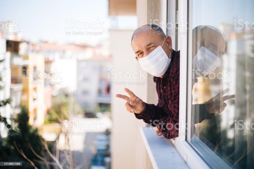 검역소에서 신선한 공기를 호흡 하는 창에 의료 마스크에 노인 - 로열티 프리 COVID-19 스톡 사진