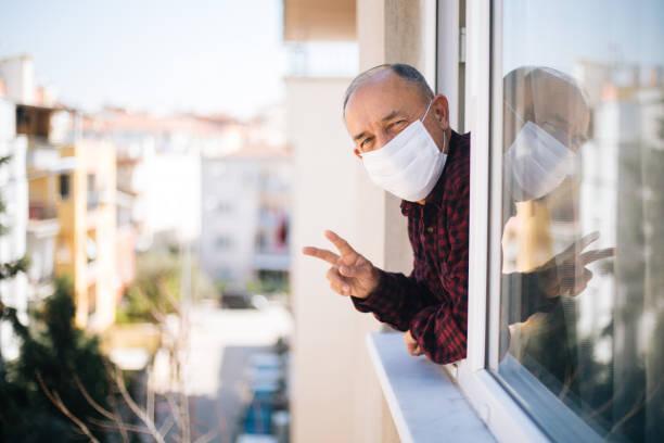 senior mann in medizinischer maske auf fenster atmen frische luft aus quarantäne - einzelner senior stock-fotos und bilder