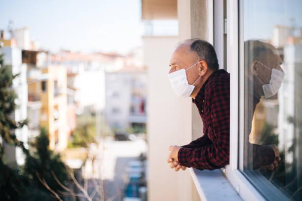 검역소에서 신선한 공기를 호흡 하는 창에 의료 마스크에 노인 스톡 사진