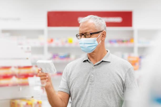 senior man in medical mask with drug at pharmacy stock photo