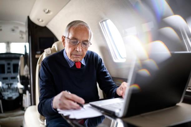senior woman im privat-jet flugzeug - wie lange leben fliegen stock-fotos und bilder