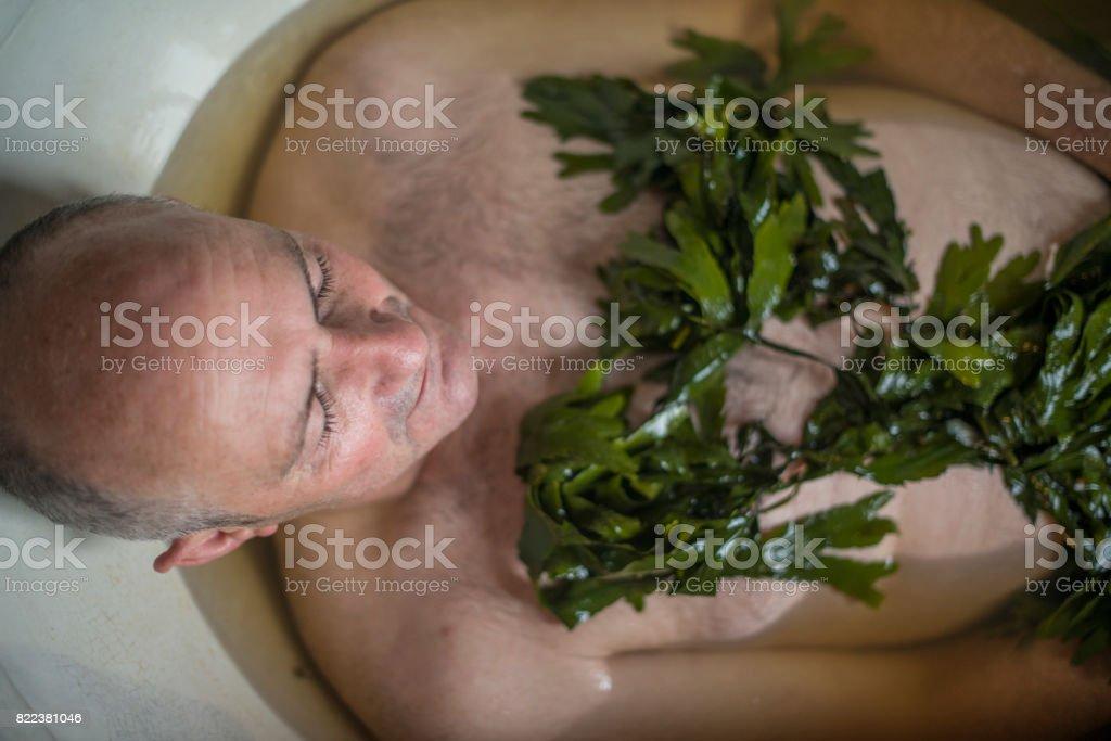 Senior man in seaweed bath royalty-free stock photo