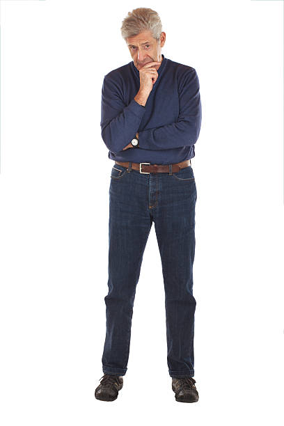 Senior man in thoughtful pose Senior man stands, arms crossed, with one hand on chin in thoughtful full length pose. He faces forward, wearing dark blue jeans and v-necked longsleeved shirt. Vertical format isolated on white. face down stock pictures, royalty-free photos & images