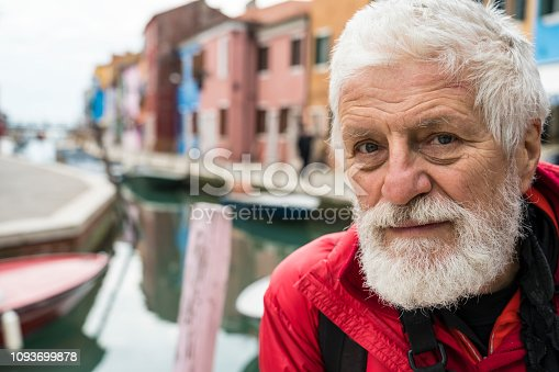 Portrait of senior man against canal and colorful facades of old village on island Burano.