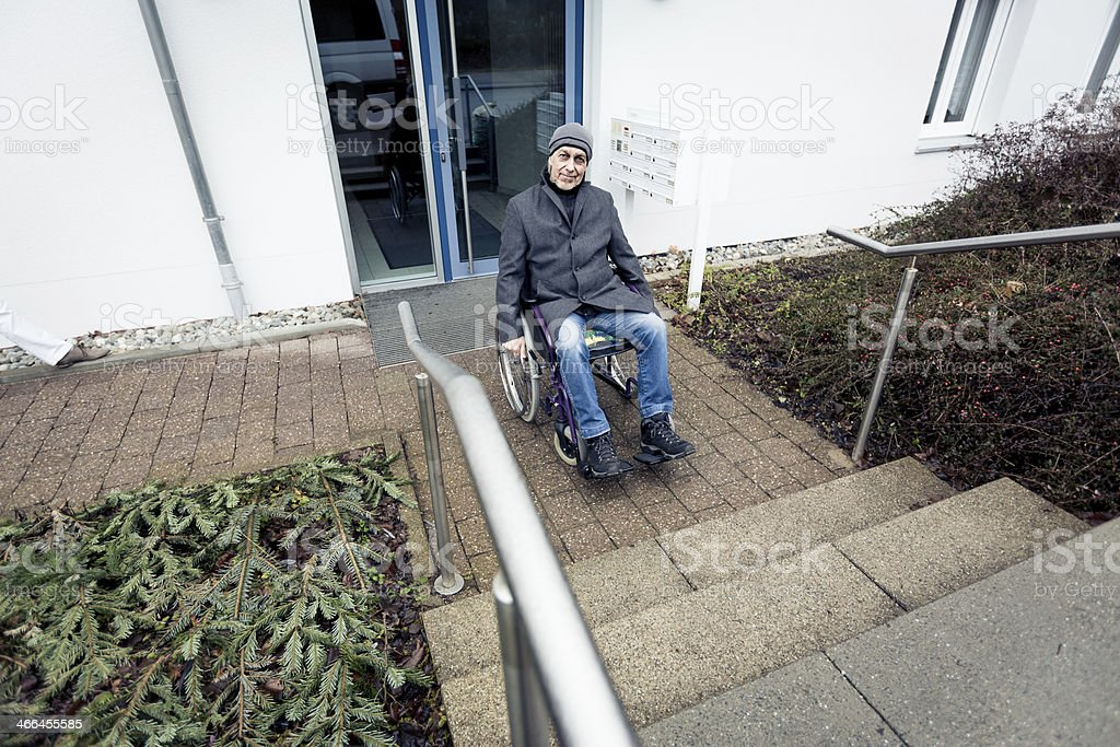 senior man in wheelchair can't go up stairs stock photo