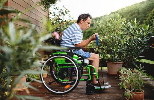 Senior man in wheelchair doing exercise on terrace.