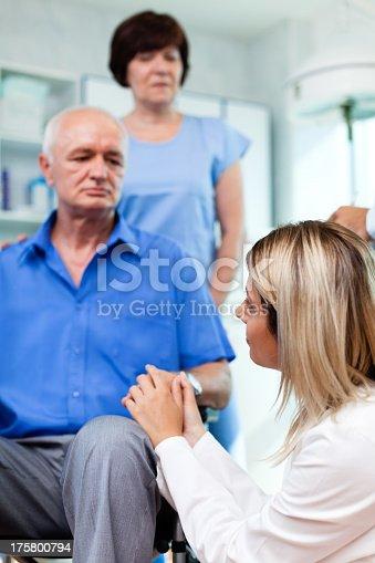 istock Senior man in wheelchair holding female doctor's hand 175800794