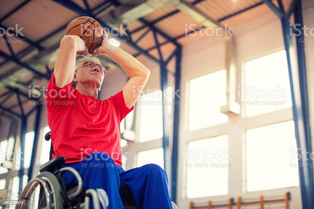 Hombre mayor en silla de ruedas jugando baloncesto - foto de stock
