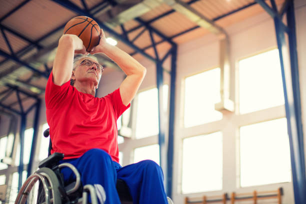 senior man in wheelchair playing basketball - wheelchair sports stock photos and pictures