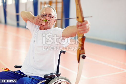 istock Senior man in wheelchair practicing archery 681388900