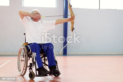 istock Senior man in wheelchair practicing archery 681389306