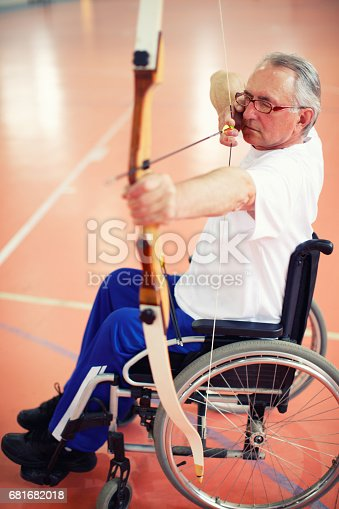 istock Senior man in wheelchair practicing archery 681682018