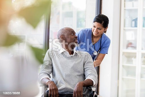 A senior man sits in a doctor's office in a wheelchair.  He smiles back at a cheerful mid adult female doctor behind him.  The doctor prepares to push his chair.