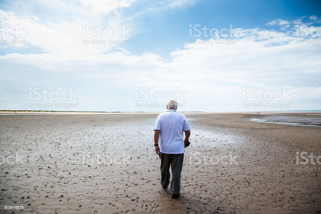 senior man in white t-shirt walks on empty wet beach in Brancaster  Norfolk England stock photo