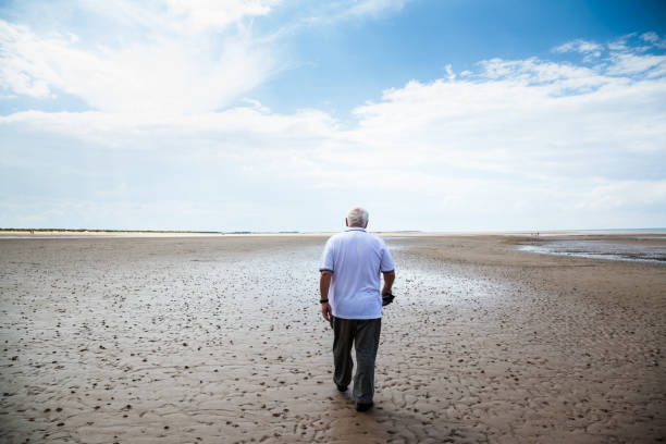 senior man in white t-shirt walks on empty wet beach in Brancaster  Norfolk England summer day one senior man only stock pictures, royalty-free photos & images