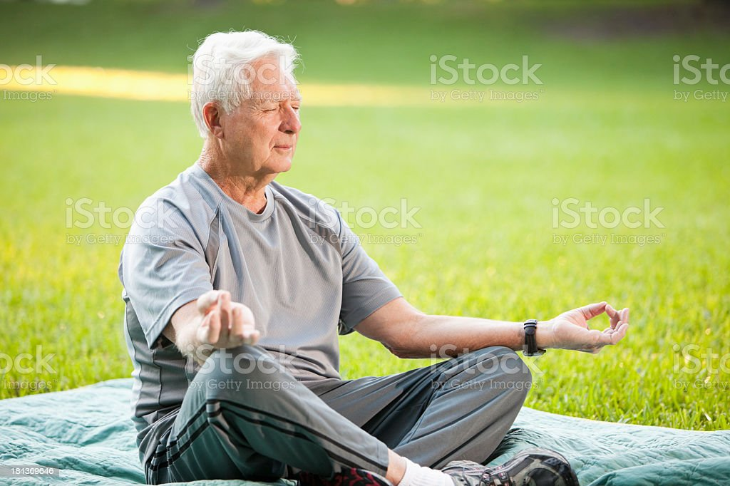 Senior man in yoga pose stock photo