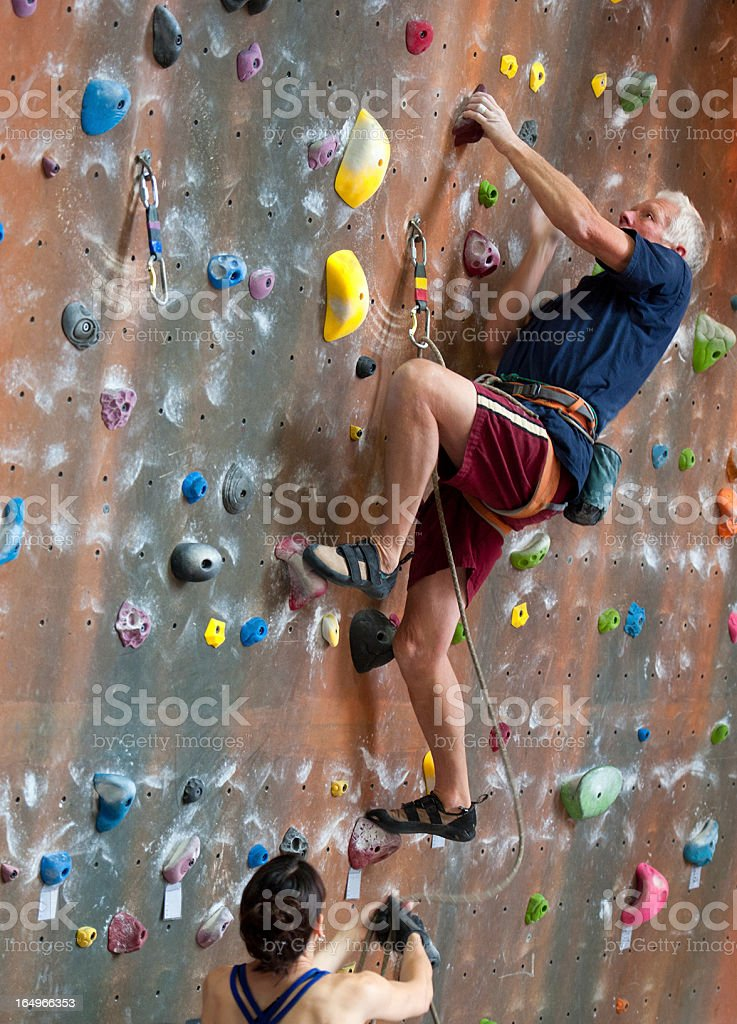 Senior Man Indoor Rock Climbing stock photo
