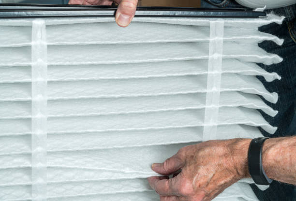 Senior man inserting a new air filter in a HVAC Furnace stock photo