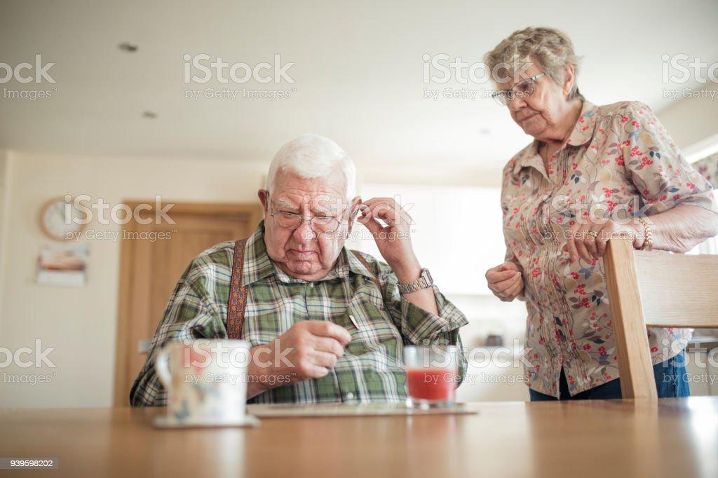 Senior Man Inserting His Hearing Aid - foto stock
