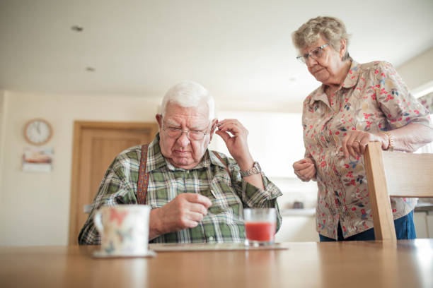 senior man inserting his hearing aid - hearing loss stock pictures, royalty-free photos & images