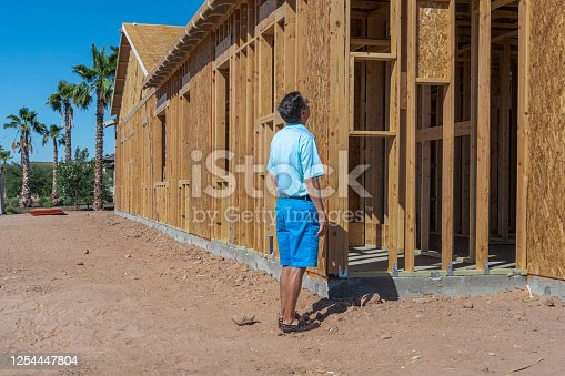 A senior man inspects the construction of a home being built in a desert community.  Possibly his retirement home.