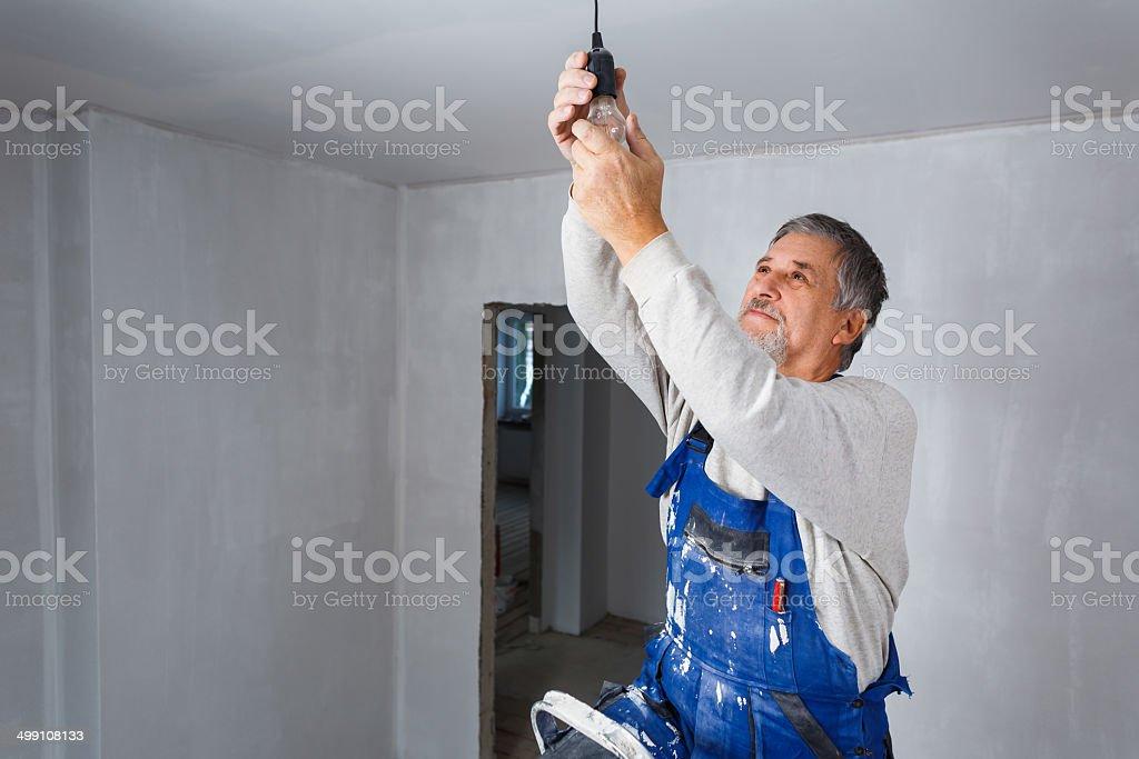 Senior man installing a bulb stock photo