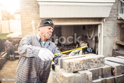 istock Senior man installing paving stones in front of his house 862283402