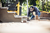 Senior man installing paving stones in front of his house