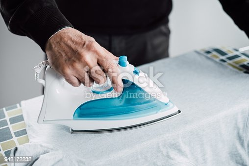 524159504 istock photo Senior man ironing the laundry 942172232