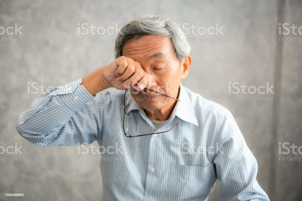 Senior man is holding eyeglasses and rubbing his tired eyes while...