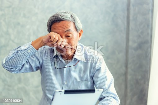 626964348istockphoto Senior man is holding eyeglasses and  rubbing his tired eyes while reading e-book in tablet 1052910934