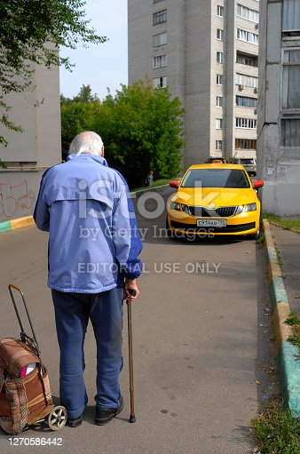 Moscow region, Russia - September 04, 2020: Senior man is pulling wheeled shopping bag on the street