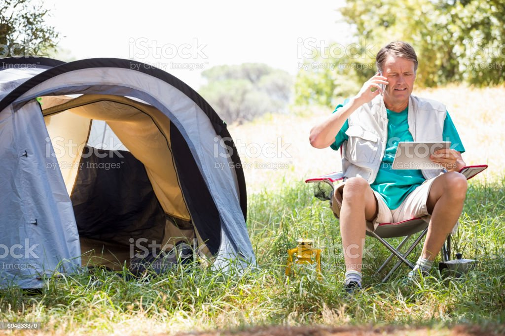 senior man is reading and talking on the phone royalty-free stock photo