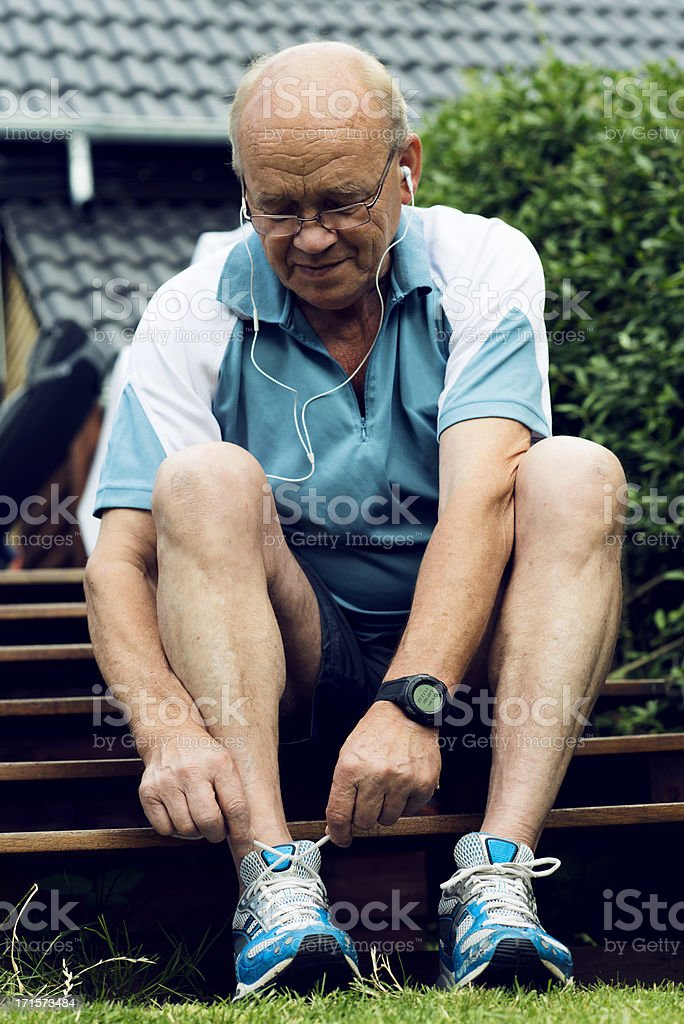 Senior man is tying a sports shoe before running royalty-free stock photo