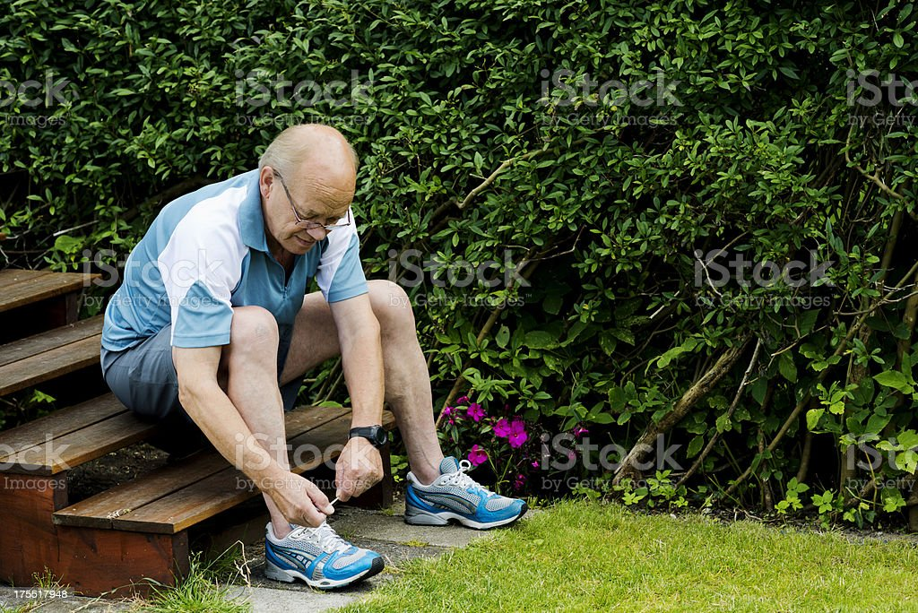 Senior man is tying a sports shoe before running stock photo
