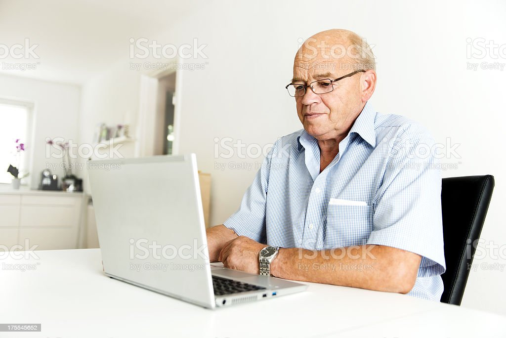 Senior man is working with a laptop royalty-free stock photo