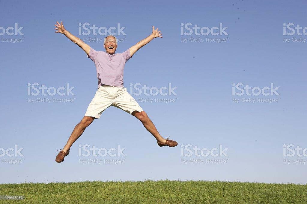 Senior man jumping in air stock photo