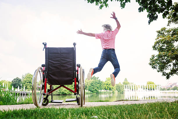 Senior man jumping up from his wheelchair - foto de stock