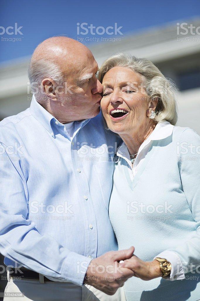 Senior Man Kissing Wife On Cheek royalty-free stock photo